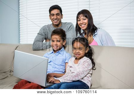 Smiling family using laptop on the sofa in living room