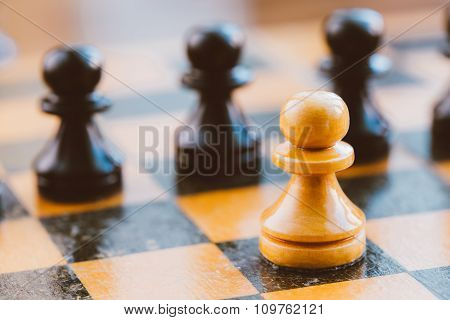 White and black chess pawns standing on chessboard