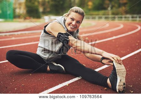Athletic Young Woman Stretching On Track Field