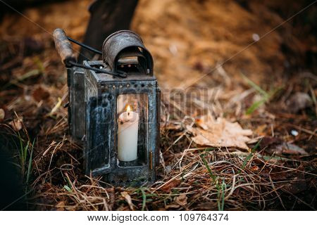 Old vintage military lantern with burning candle