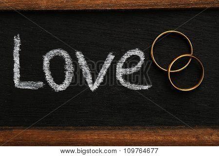Golden Wedding Rings On The Wooden Frame