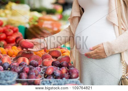 sale, shopping, pregnancy and people concept - close up of pregnant woman choosing saturn peaches at street food market