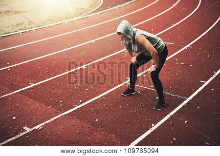 Young Female Runner Standing On Stadium And Listening To Music