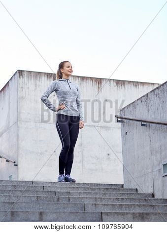 fitness, sport, people and lifestyle concept - smiling sportive woman on stairs at city