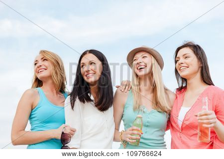 summer holidays and vacation concept - girls with drinks on the beach