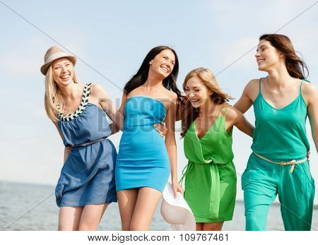 summer holidays and vacation concept - smiling girls walking on the beach