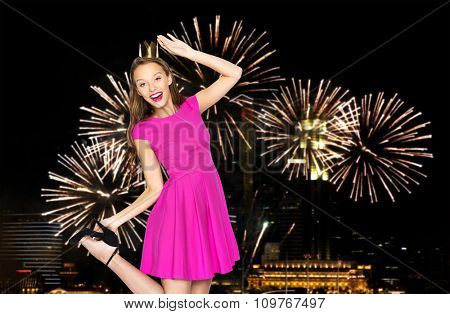 people, holidays, party and fashion concept - happy young woman or teen girl in pink dress and princess crown over firework at night singapore city background