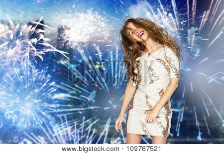 people, style, holidays, hairstyle and fashion concept - happy young woman or teen girl in fancy dress with sequins and long wavy hair dancing at party over firework at night city background