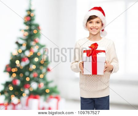 holidays, christmas, childhood and people concept - smiling happy boy in santa hat with gift box over living room background