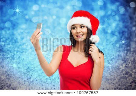 people, holidays, christmas and technology concept - beautiful sexy woman in red santa hat taking selfie picture by smartphone over blue glitter and lights background