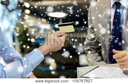 auto business, sale and people concept - close up of customer giving credit card to car dealer in auto show or salon over snow effect