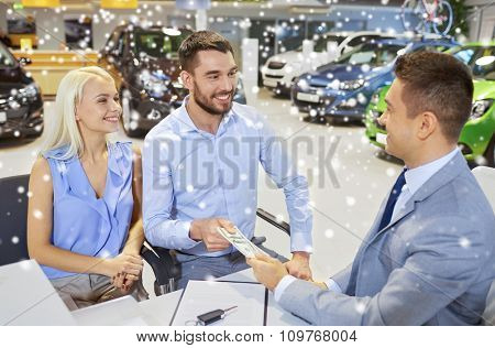 auto business, sale and people concept - happy couple with money buying car from dealer in auto show or salon over snow effect