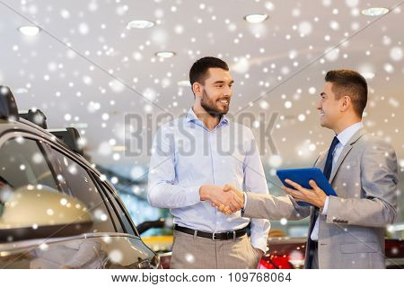 auto business, car sale, technology, gesture and people concept - happy man and car dealer with tablet pc computer shaking hands in auto show or salon over snow effect