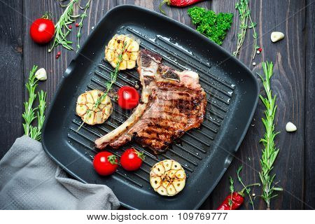 Steak with herbs and pepper on cooking pan over dark wooden background