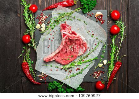 Raw fresh meat Steak with salt, pepper and rosemary on dark wooden background