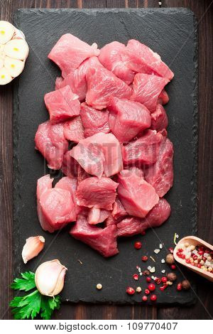 Raw chopped fresh meat with pepper and herbs over dark stone cutting board