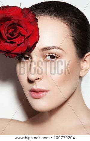Portrait of young beautiful woman with glowing make-up and red rose