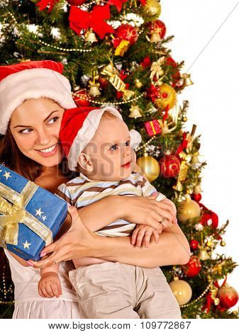 Mom wearing Santa hat holding  baby with blue gift box  under Christmas tree on isolated.