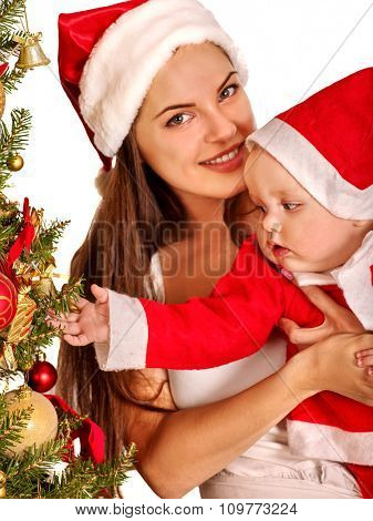 Mom wearing Santa hat holding  baby decorating Christmas tree.