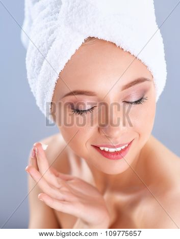 Beautiful young woman applying a creme on her face isolated on gray background