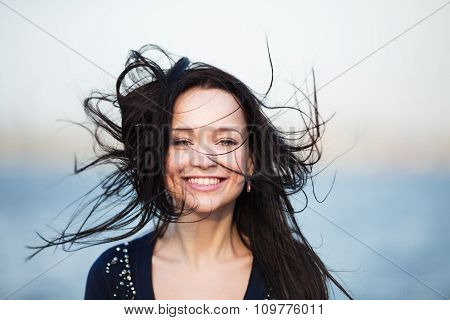 Smiling girl with long black hair blowing by wind