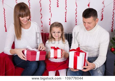 Happy Family Sitting On Sofa And Opening Christmas Gifts