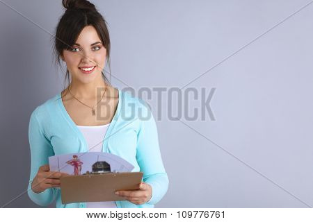 Woman with folder for documents on gray  background