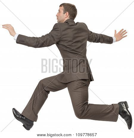 Businessman in suit running on white