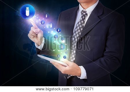 Businessman holding tablet with pressing usb flash drive icon button. internet and networking concep