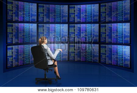 Businesswoman sitting in front of screens