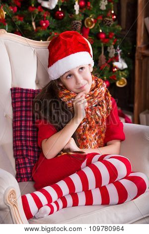 Beautiful Santa girl dreaming near the Christmas tree, making a wish. New year interior
