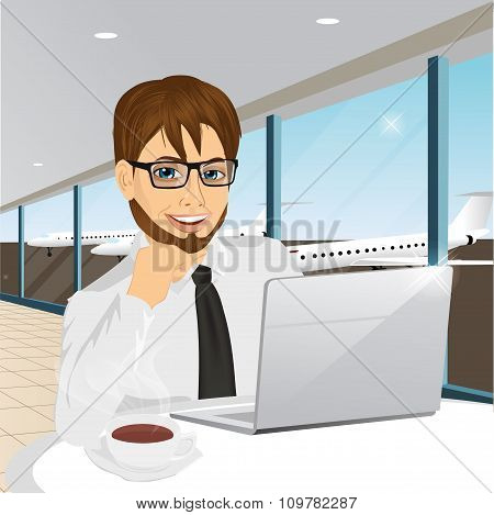 businessman working at laptop at airport
