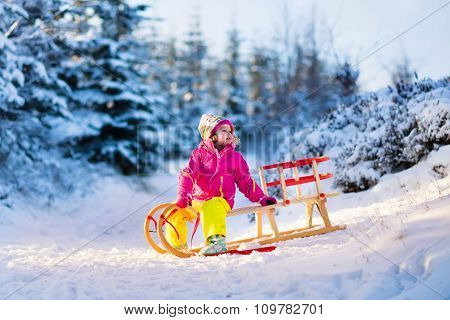 Little Girl Having Fun On A Sledge In Snowy Winter Forest