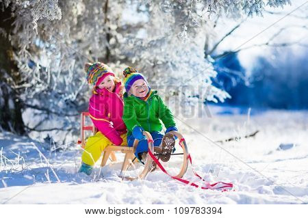 Kids Riding A Sleigh In Snowy Winter Park