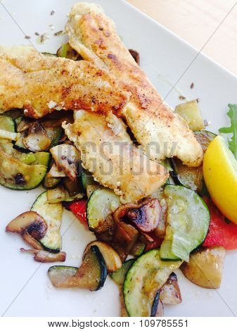 Grilled battered fish and fried vegetables served on plate in restaurant