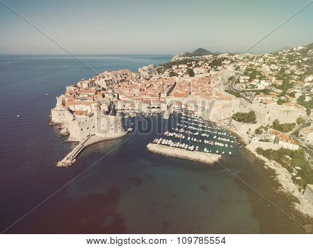 Aerial view of old city of Dubrovnik (Croatia) with old port in front. Dubrovnik is popular tourist attraction on Adriatic. Post processed with vintage filter.