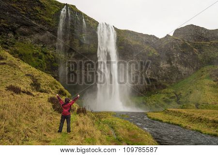 Happy Woman By Waterfall Skogafoss On Iceland Posing Serene And Free Outdoors With Arms Raised.