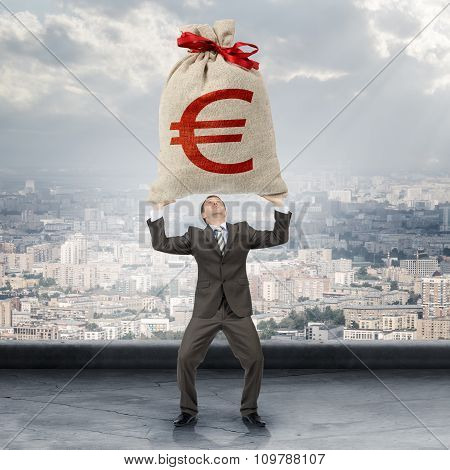 Businessman holding big moneybag with euro sign