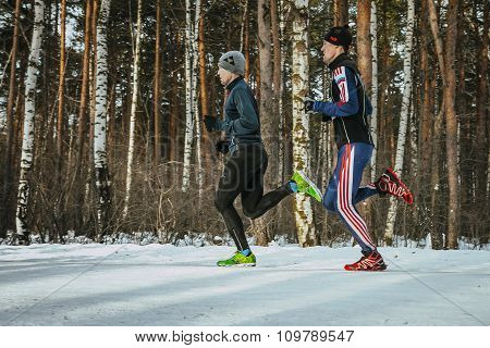 two men athletes running through woods