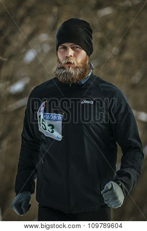male athlete with a lush beard runs