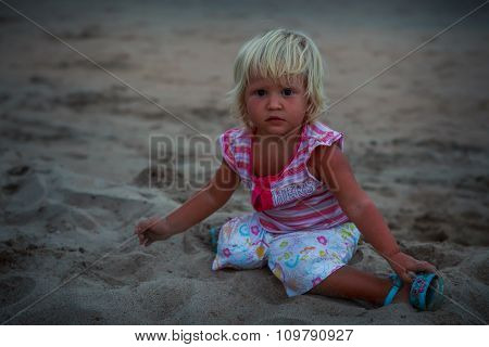 Small Blonde Girl In Colorful Sits On Beach Sand Looks Forward