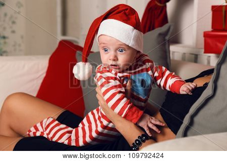 Cute Little Santa Baby Sitting At Mom's Hands At Cozy Home With New Year Decoration