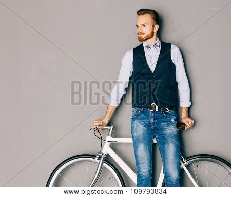 A young man with mustache and beard is near fashionable modern fixgear bicycle. Jeans and shirt, ves