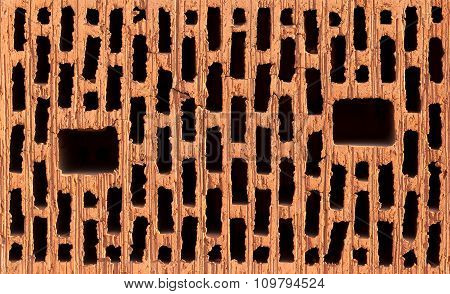 Front view of red brick with holes isolated on black background