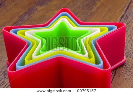 Rainbow Plastic Stars on Wooden Background