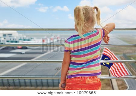 Young Passenger Looks At Planes In Airport