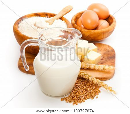 Glass Jug With Milk, Wheat Seeds, Flour And Two Eggs On White Background