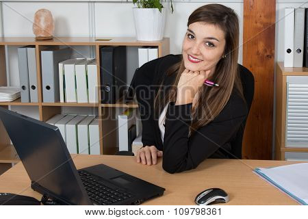 A Business Woman Is Concentrating On Screen With Pen In Her Hand