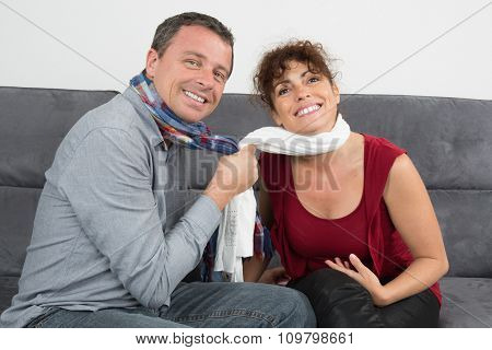 Middle Aged Couple Relaxing On The Couch Smiling At Camera
