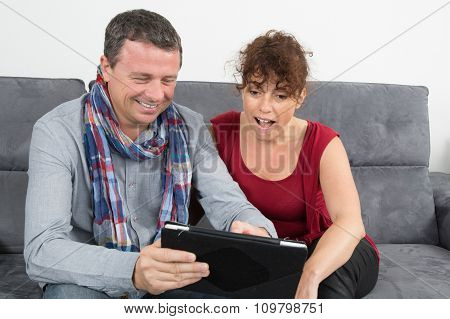 Happy Couple Looking For Tv Program On Tablet
